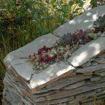 Havemur bygget af knækfliser i sandsten