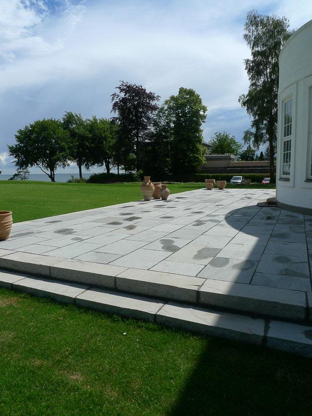Stor terrassemed grå sandsten og lang trappe mod græsplæne