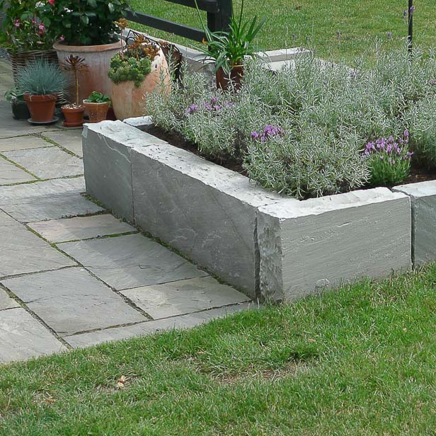 Lille højbed med lavendel bygget af blokke af sandsten