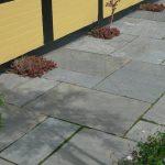Chelsea fliser i mønster med plantehuller mod husvæg