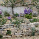 Rustik mur af sandsten foran stenbed