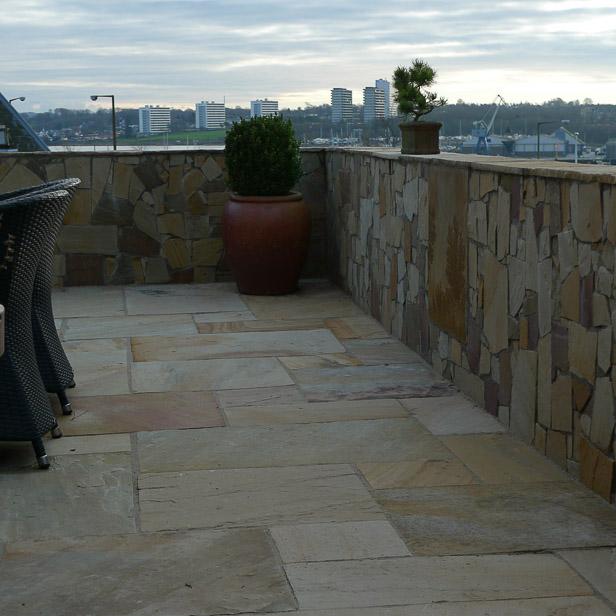 Støttevæg omkring stor terrasse, sandsten på terrasse og væg