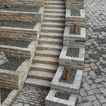 Indkørsel med støttemure og plantekummer på begge sider af høj trappe i Sandstone Dark. Bygget af murblokke og trappetrin. Fliser også sandsten.