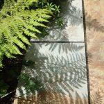 natursten sandsten Sandstone Ellipseformet terrasse i Sandstones udstilling i Sorø, mosbregne laver skygge på naturstenen