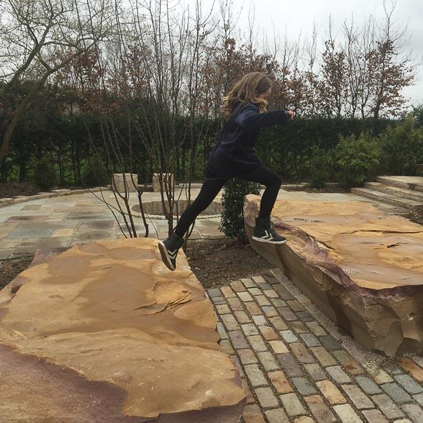 Pige laver parkour på sandstensblokke